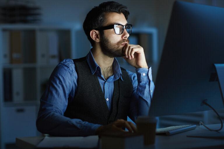 Mężczyzna pracuje w nocy przed komputerem