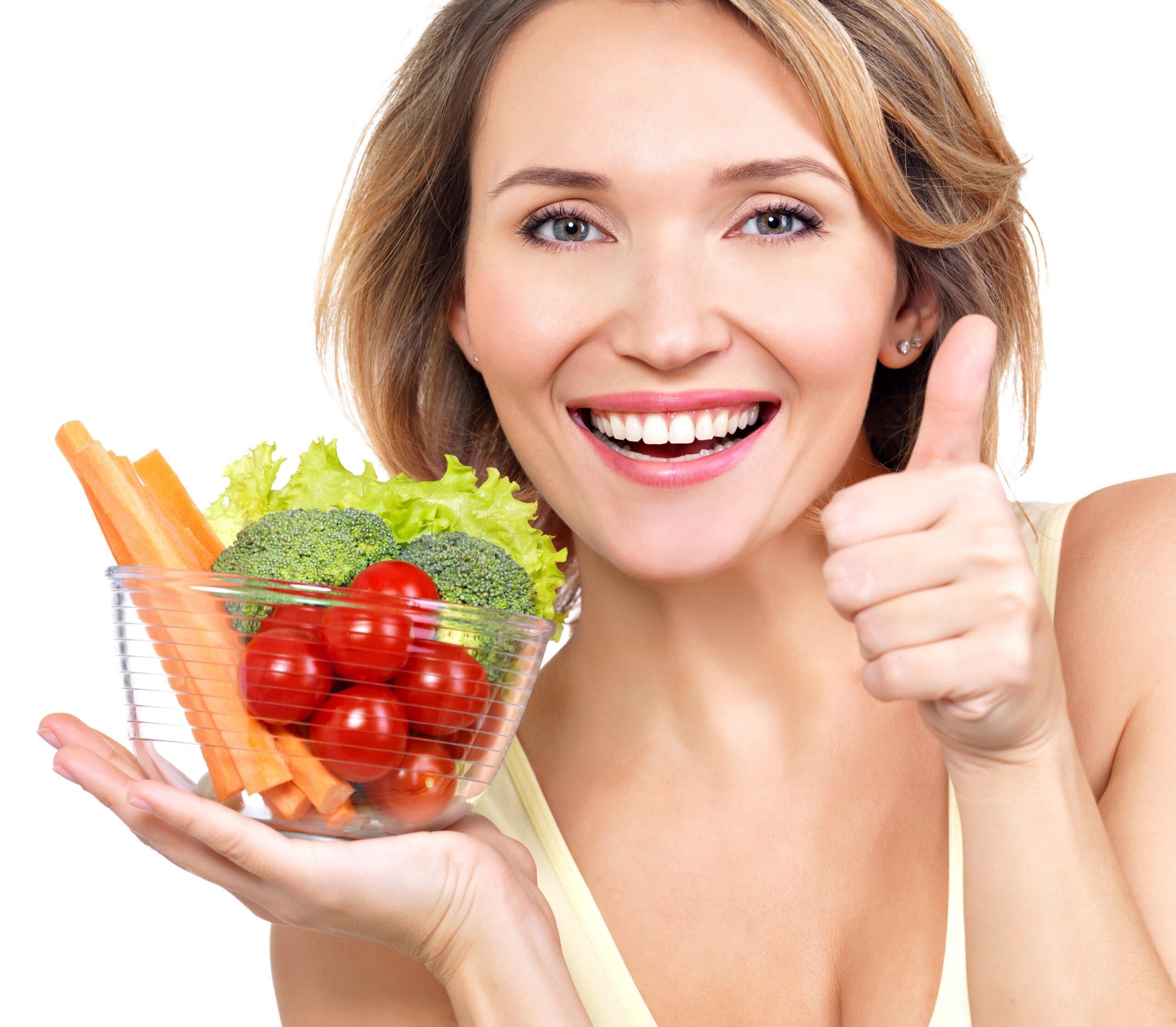 Uśmiechnięta kobieta zmiską warzyw
