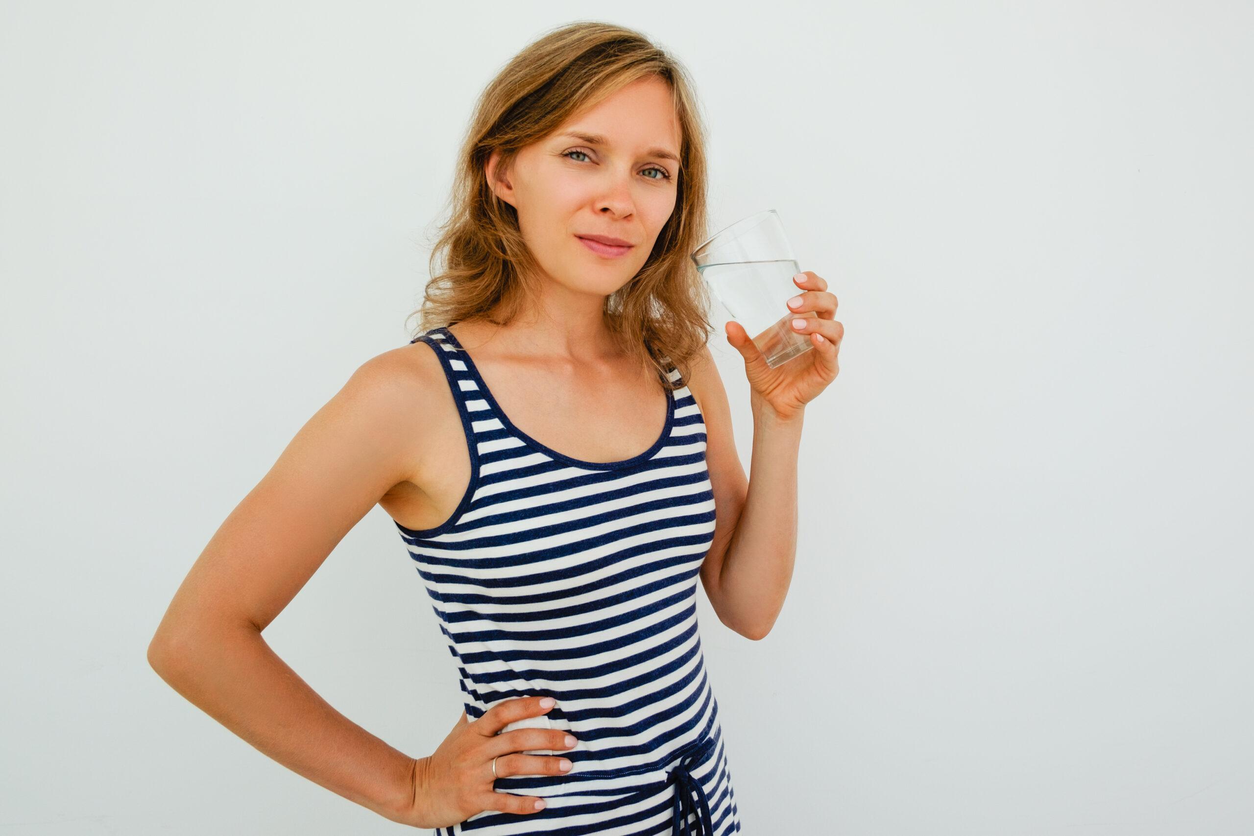 Przesilenie wiosenne - nawadnianie organizmu. Kobieta trzyma szklankę wody.