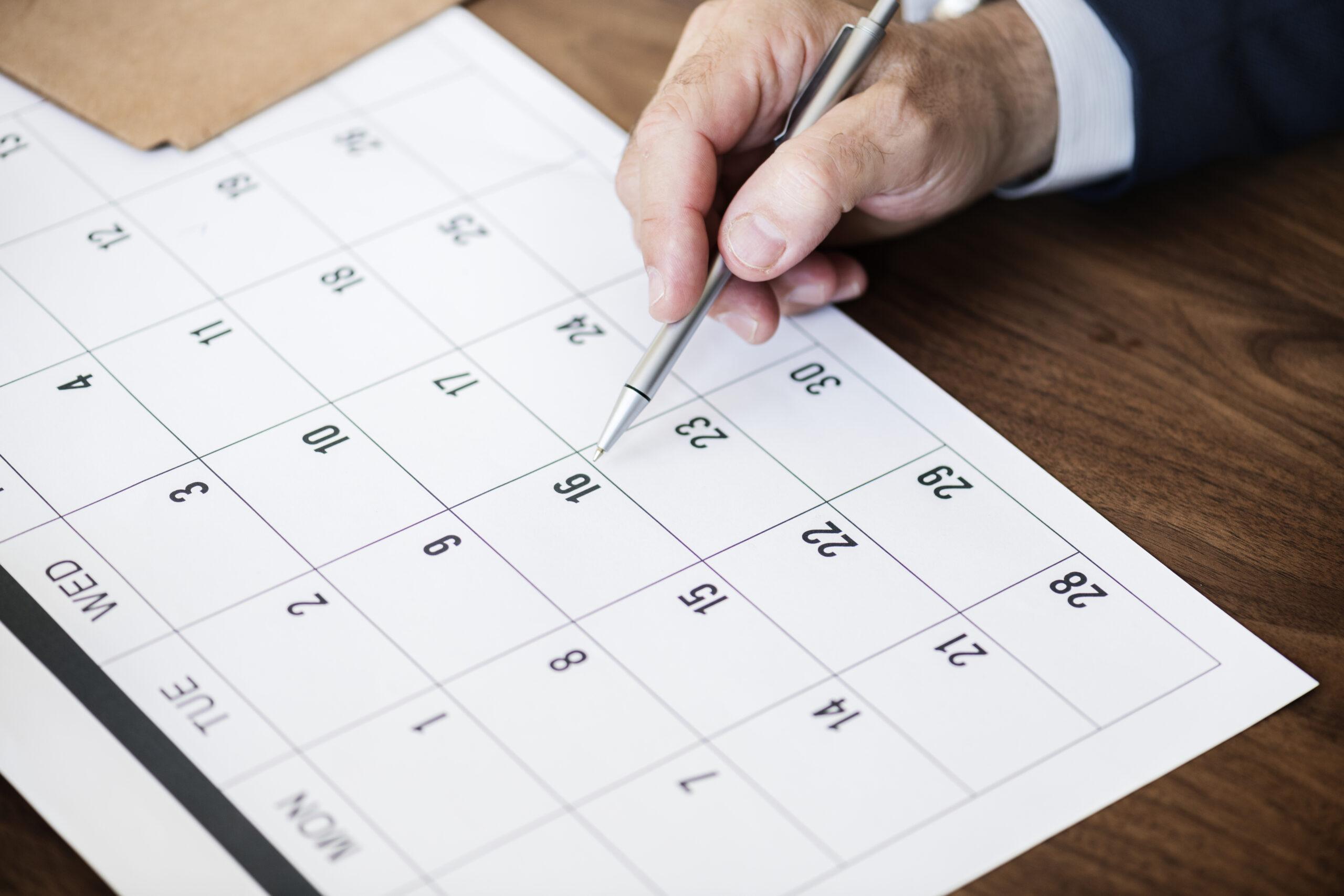 Kartka zkalendarza iręka mężczyzny zdługopisem