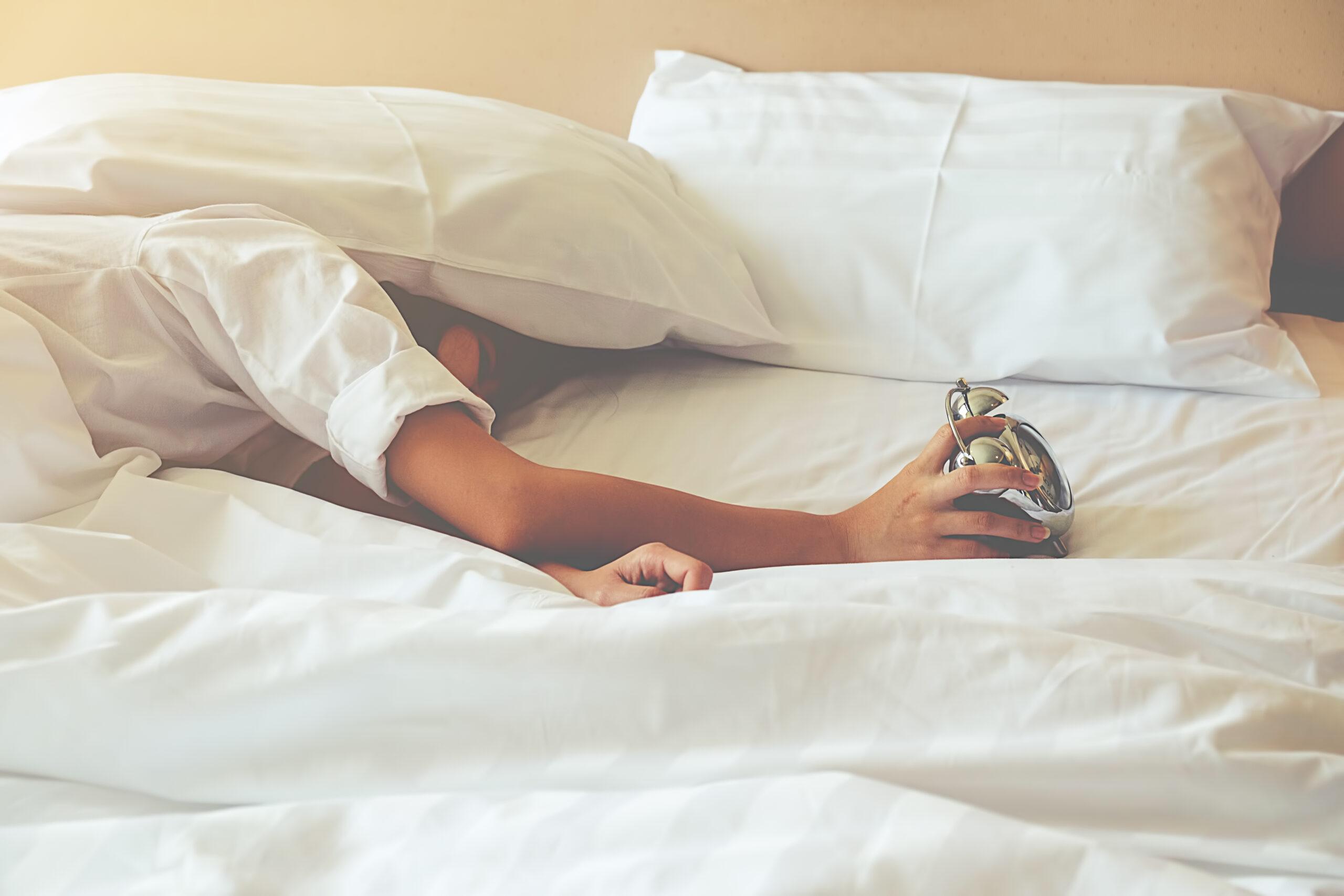 Kobieta śpi itrzyma wręku zegarek