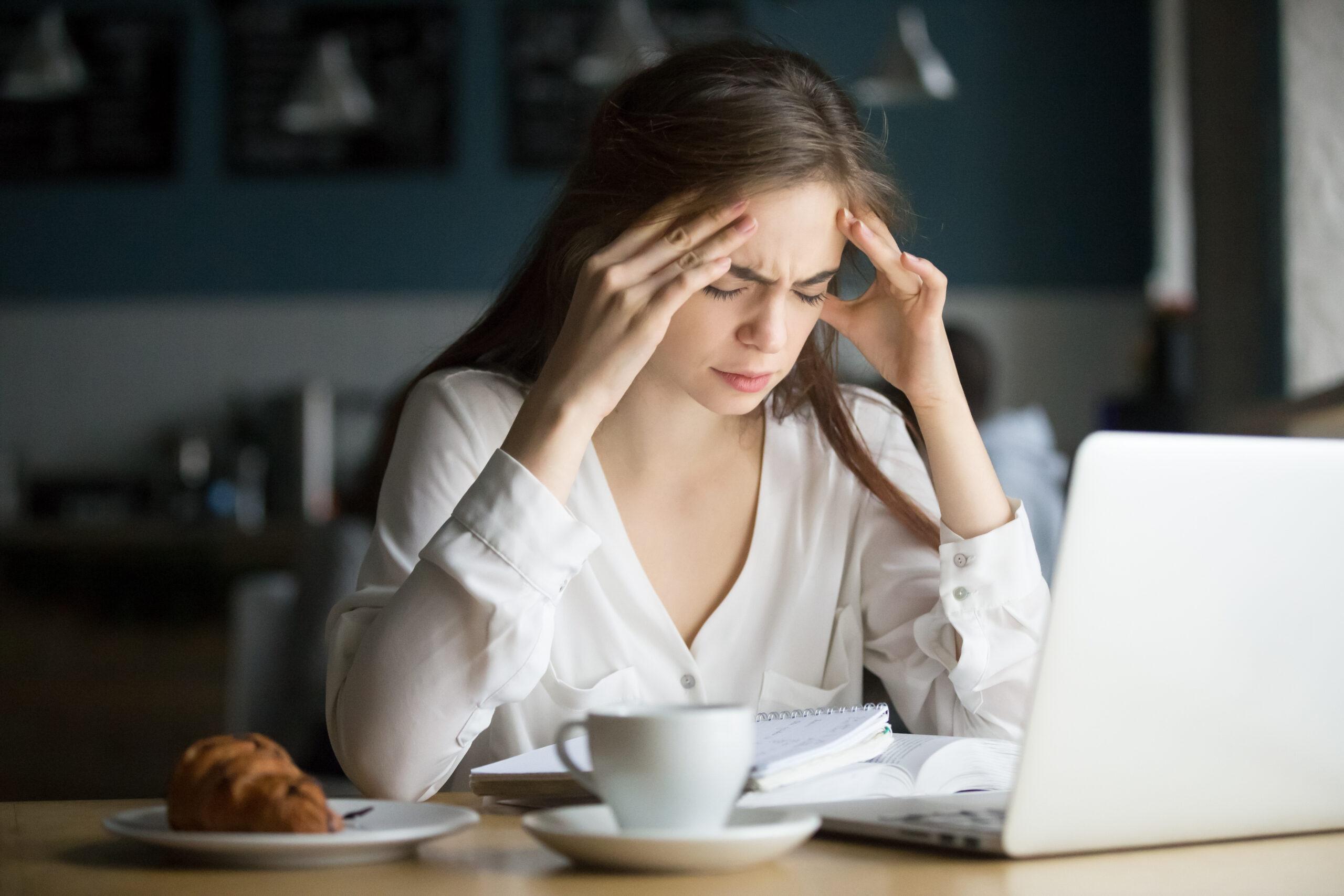 Kobieta zbólem głowy, siedzi przed laptopem