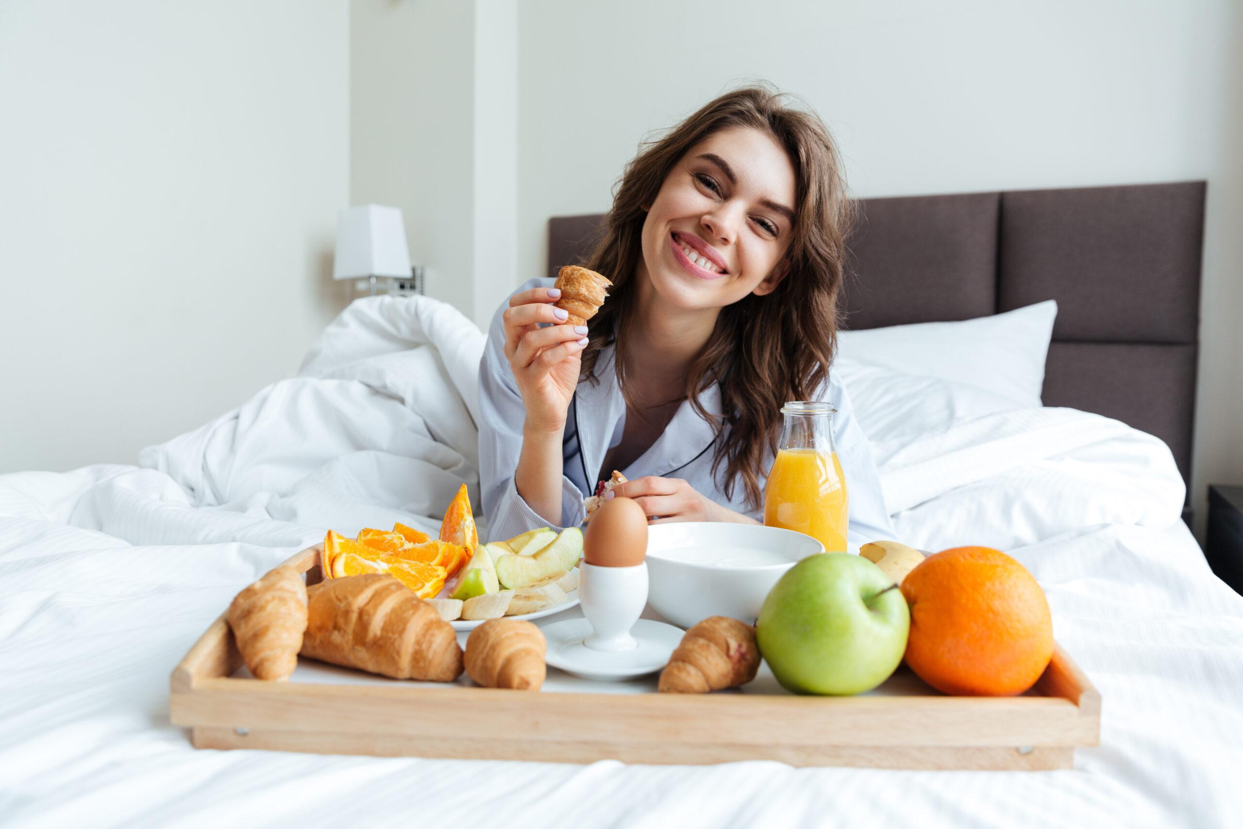 Uśmiechnięta kobieta je śniadanie włóżku